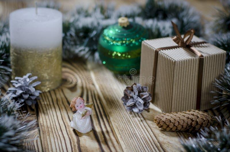 En gåva lägger på en trätabell bredvid en stearinljus, kottar och en ängel mot bakgrunden av julpynt royaltyfria bilder