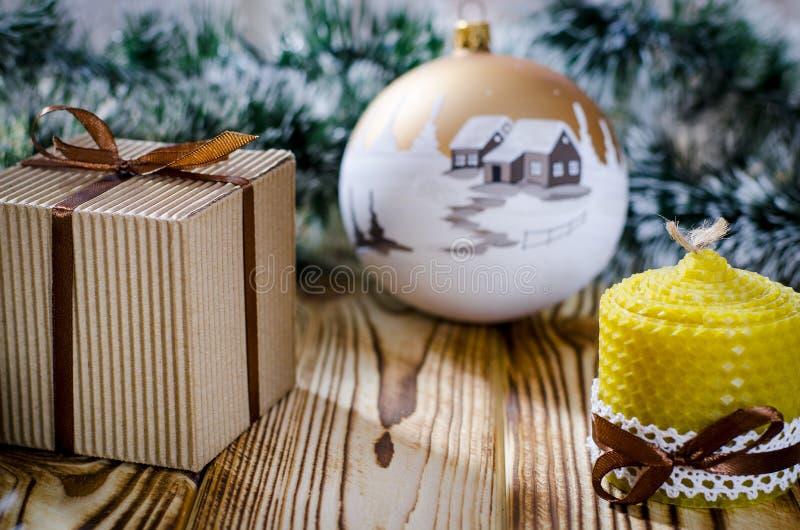 En gåva lägger på en trätabell bredvid en stearinljus, kottar och en ängel mot bakgrunden av julpynt royaltyfri fotografi