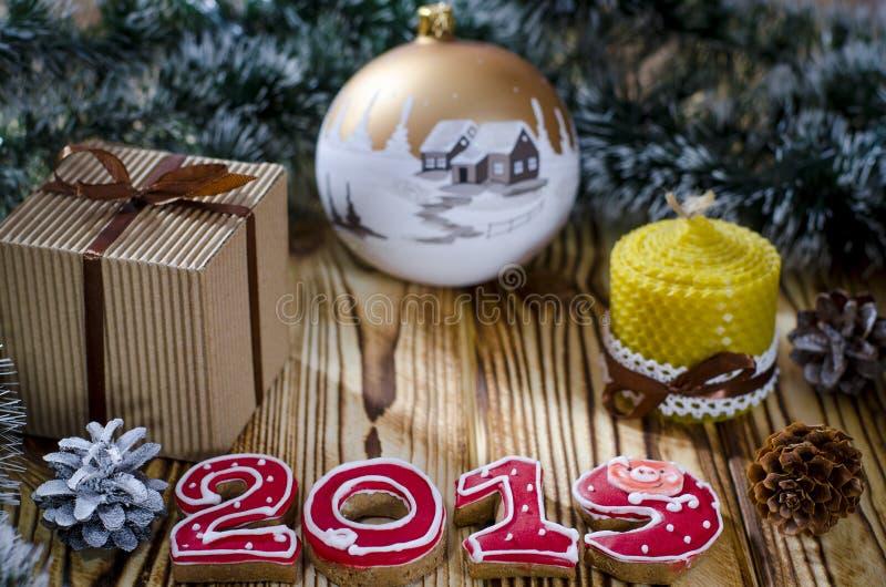 En gåva lägger på en trätabell bredvid en stearinljus, kottar och en ängel mot bakgrunden av julpynt royaltyfria foton