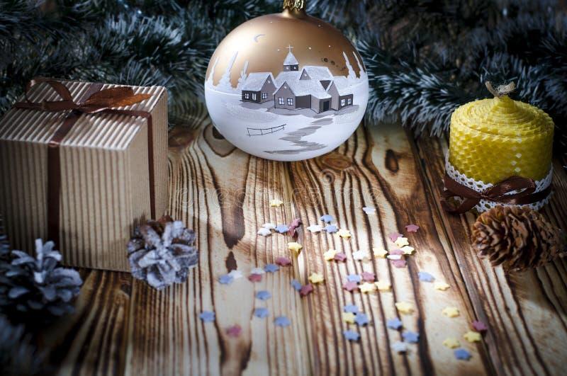 En gåva lägger på en trätabell bredvid en stearinljus, kottar och en ängel mot bakgrunden av julpynt arkivfoton