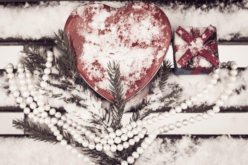 En gåvaask, röd hjärta formad tenn- ask med en vit pärlemorfärg halsband royaltyfria foton