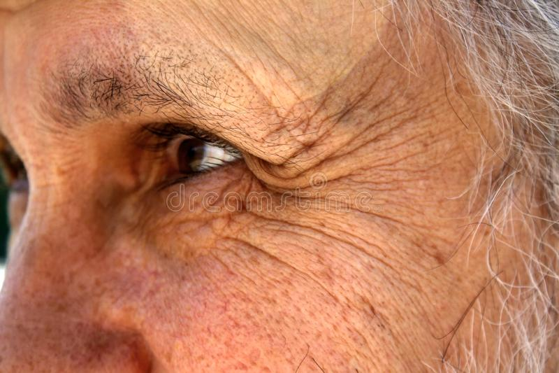 En gamal man med djupa skrynklor nära ögonen ser in i avståndet arkivfoto