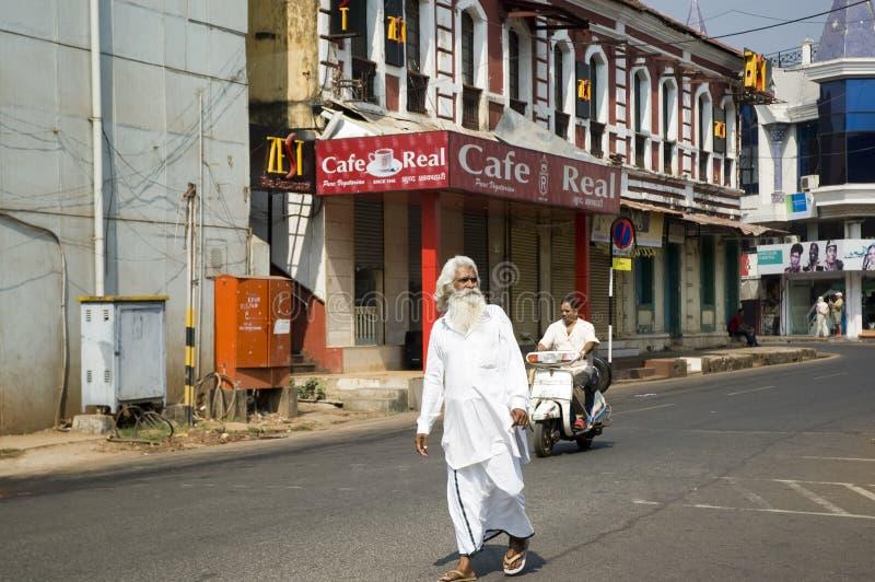En gamal man med ett gr?tt sk?gg i vit kl?der som g?r gatorna av staden Indien Goa - 29 Januari 2009 royaltyfria bilder