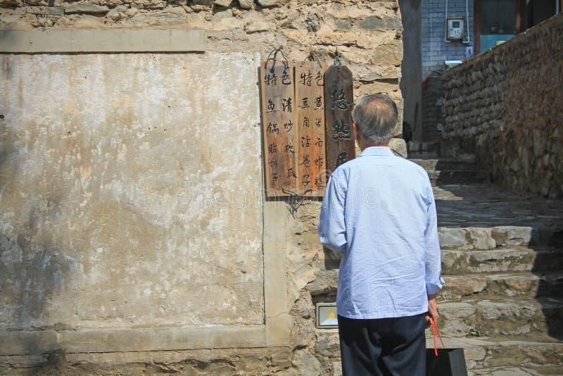 En gamal man som läser tecknet royaltyfri bild
