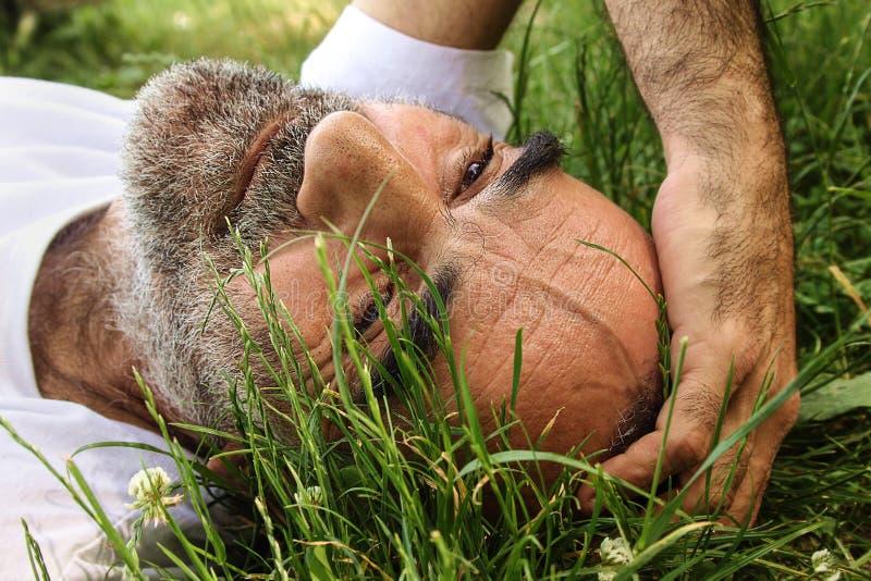 En gamal man som ligger på gräset royaltyfria foton