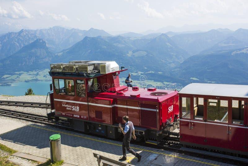 En gammal ångalokomotiv klättrar upp 'schafbergbahnen' på till överkanten av Schafbergen arkivbild