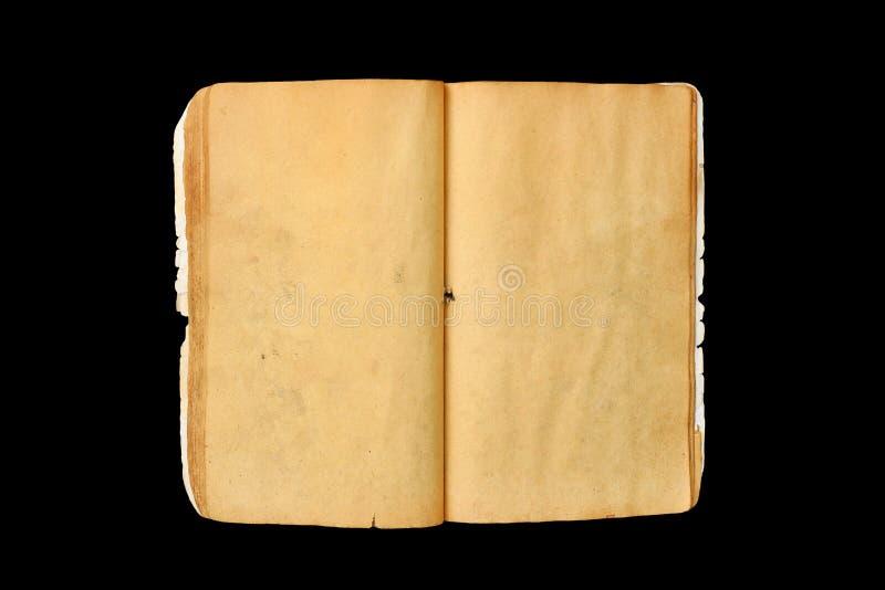 En gammal öppen bok med befläckte sidor för mellanrum som guling isoleras på svart bakgrund royaltyfria bilder