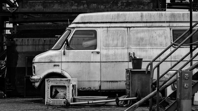 En gammal ambulans som parkeras i framdel av en gammal byggnad royaltyfria bilder