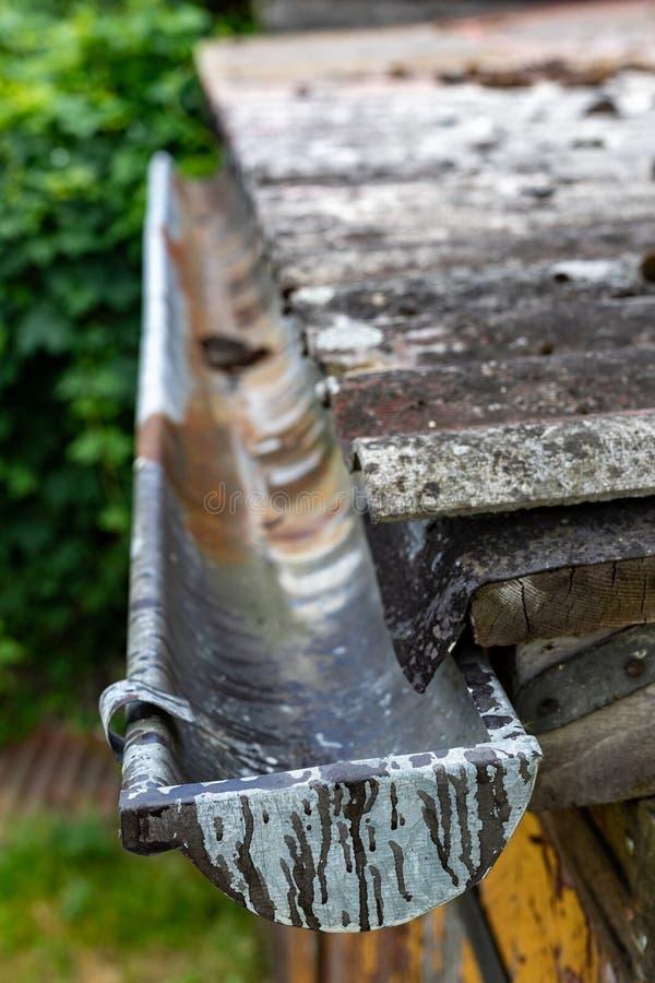 En gammal avloppsränna i en småhus Regnvattendränering från taket royaltyfri foto