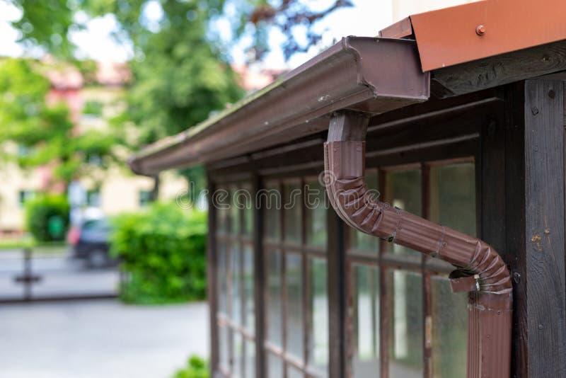 En gammal avloppsränna i en småhus Regnvattendränering från taket royaltyfria bilder