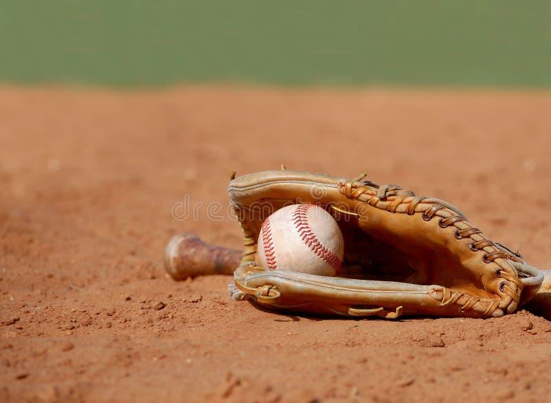 En gammal baseballhandske som vaggar en sliten boll arkivbilder
