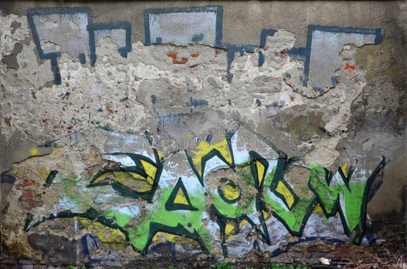 En gammal betongvägg med utan ben murbruk som är bortskämd vid den kulöra grafittiteckningen royaltyfri fotografi