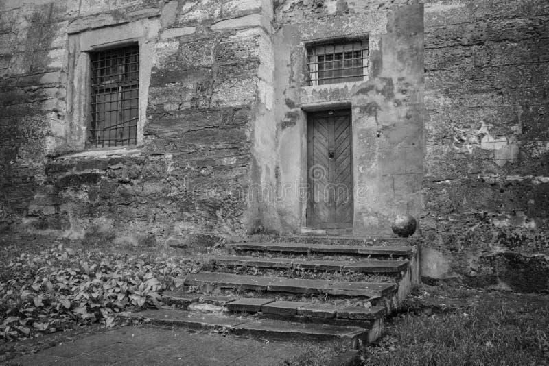En gammal byggnad med ett stängt fönster och en dörr i svartvitt royaltyfria foton