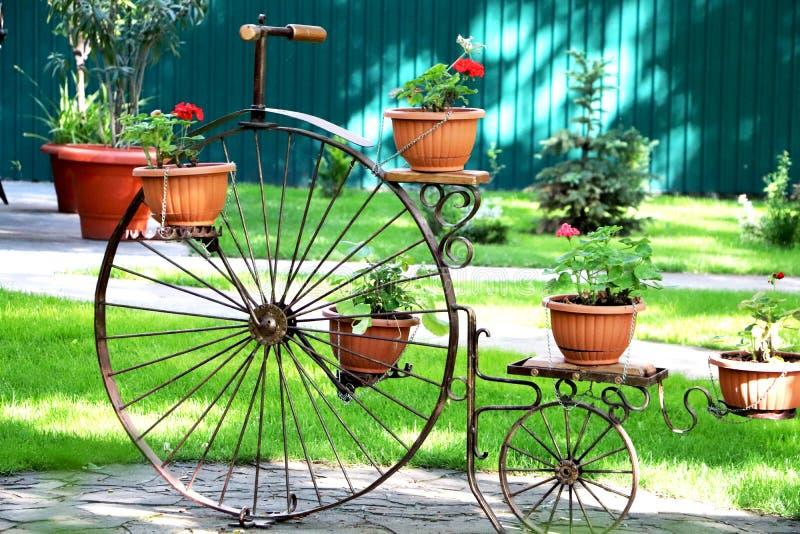 En gammal cykel med blommakorgar för att dekorera parkerar och arbeta i trädgården arkivfoton