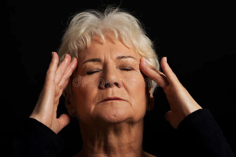 En gammal dam som har en huvudvärk. arkivfoto