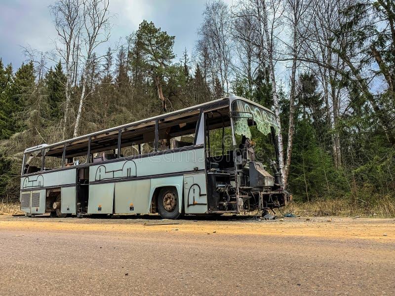 En gammal grå buss överges på en väg i skogen Skogslandskap med bortglömd gråbuss splittrad kommersiell royaltyfri foto