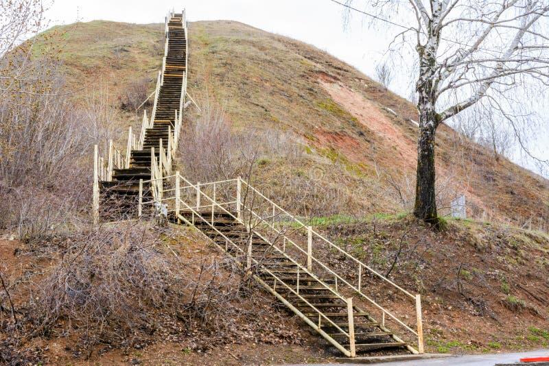 En gammal högväxt trätrappuppgång stiger på ett stort berg Stegen symboliserar tillväxt, uppstigningen, ambitionen, viljekraft Te royaltyfria bilder