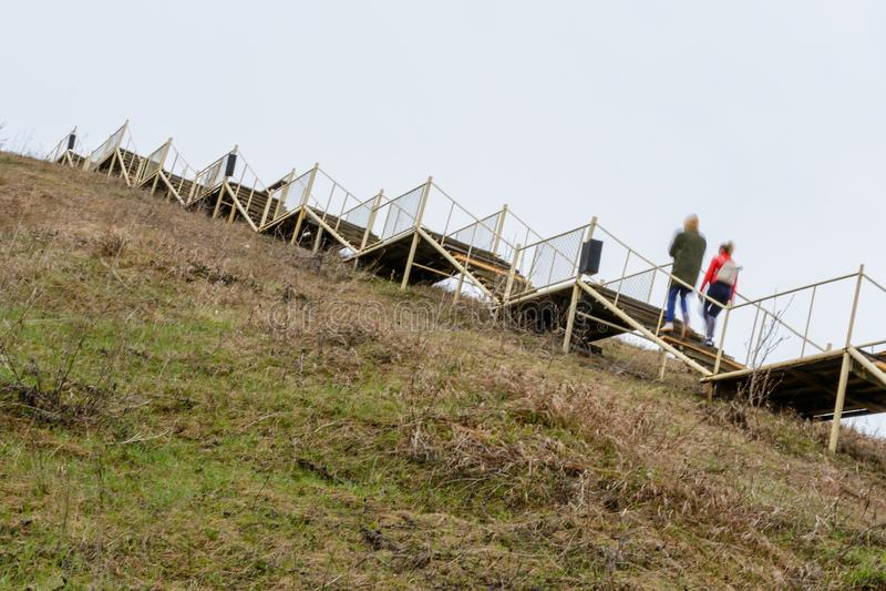 En gammal högväxt trätrappuppgång stiger på ett stort berg Stegen symboliserar tillväxt, uppstigningen, ambitionen, viljekraft Te arkivbilder