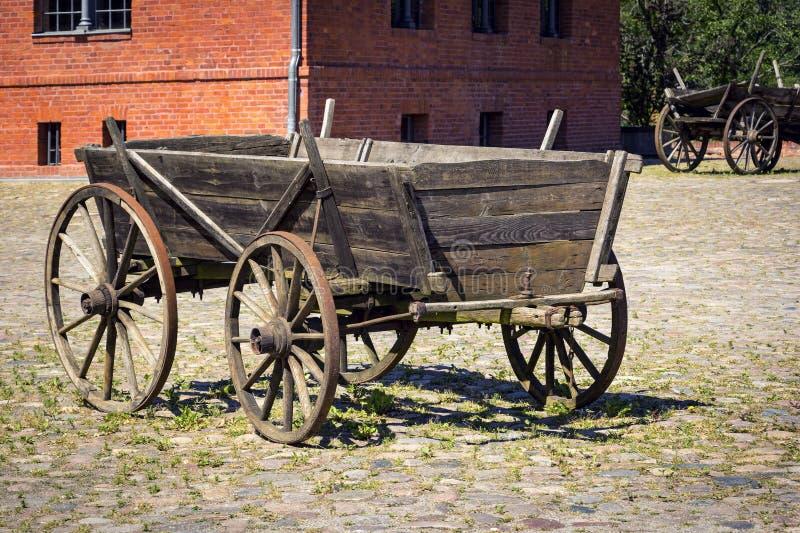 En gammal historisk vagn står i gården av en historisk lantgård royaltyfri foto