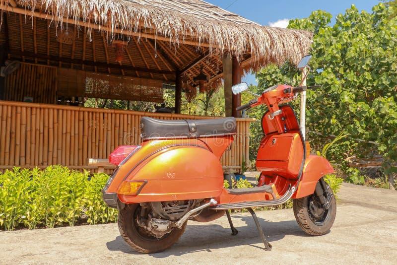 En gammal italiensk sparkcykel som framme parkeras av en bambubyggnad Orange klassisk vara nedstämd Vespa från Italien Bakgrundsb arkivfoto