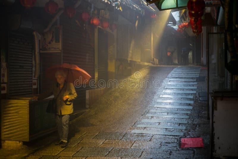 En gammal kinesisk dam med ett paraply i en mystisk tillbaka gränd och trappuppgången i den taiwanesiska byn av Jiufen arkivfoton