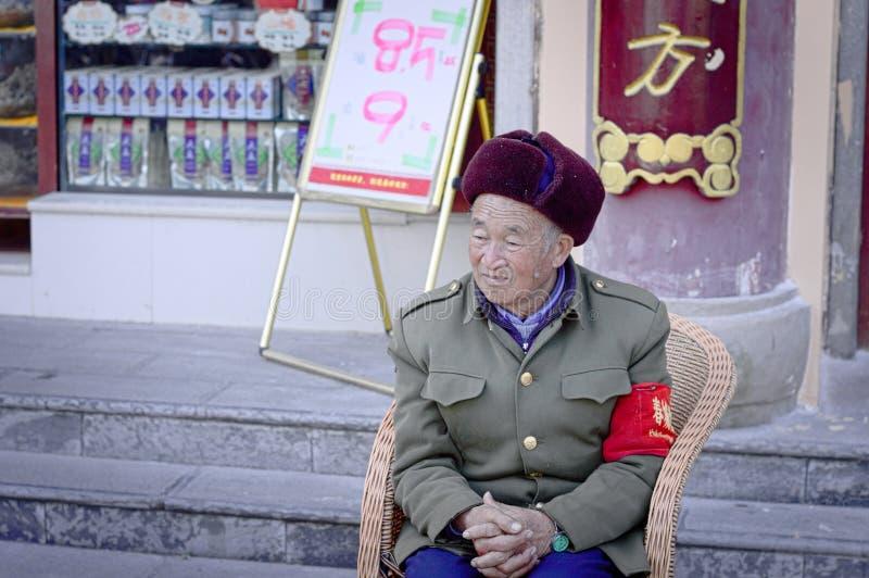 En gammal kinesisk soldat sitter utanför den Yuantong templet royaltyfria foton