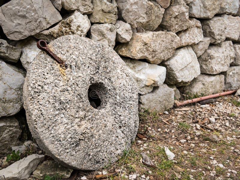 En gammal kvarnstenbenägenhet mot en stenvägg royaltyfri fotografi