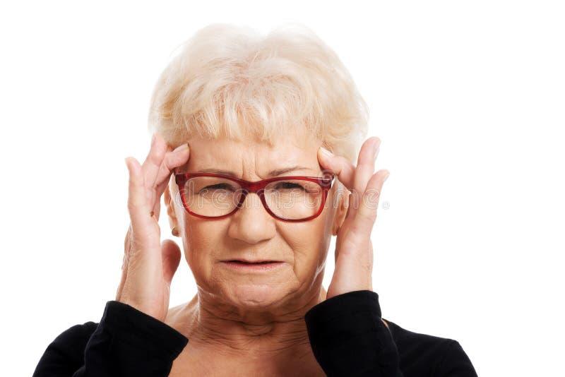 En gammal kvinna är ögonexponeringsglas har en huvudvärk. arkivbild