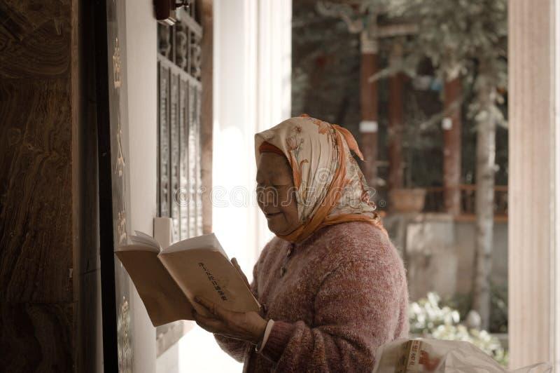 En gammal kvinna ber i den Yuantong templet royaltyfria bilder