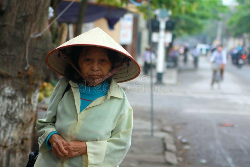 En gammal kvinna går på trottoaren till henne hem i den Nam Dinh staden i norden av Vietnam royaltyfri bild