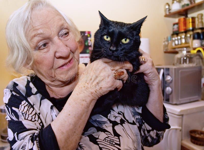 En gammal kvinna kramar hennes katt royaltyfria bilder
