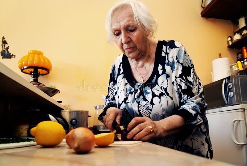 En gammal kvinna lagar mat arkivfoton