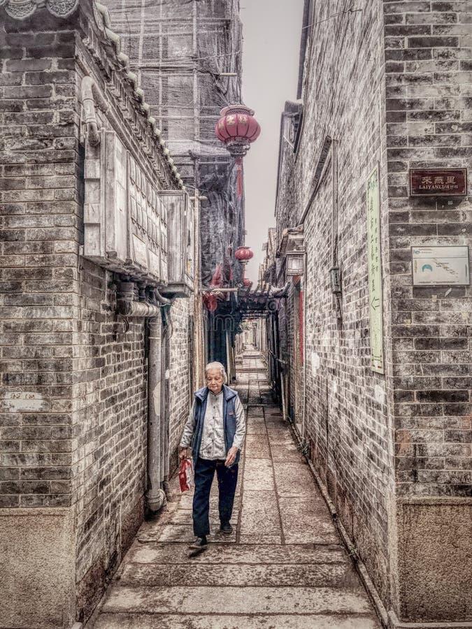 En gammal kvinna som går i gränden fotografering för bildbyråer