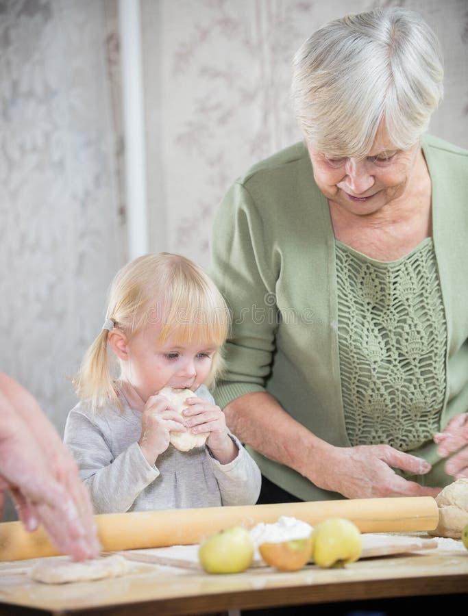 En gammal kvinna som gör små pajer med hennes sondotter Flickan som smakar degen royaltyfri bild