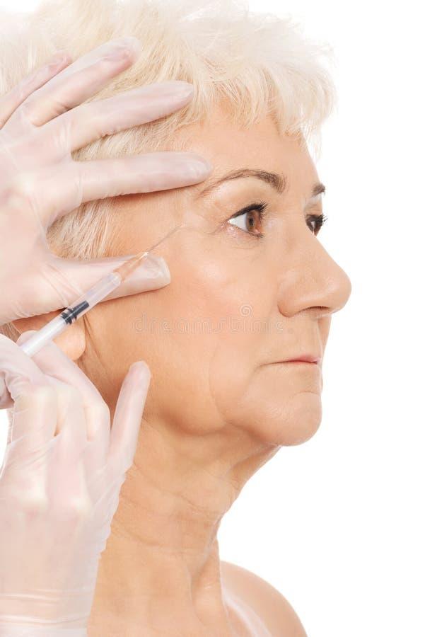 En gammal kvinna som har ett injektionskönhetbegrepp. fotografering för bildbyråer