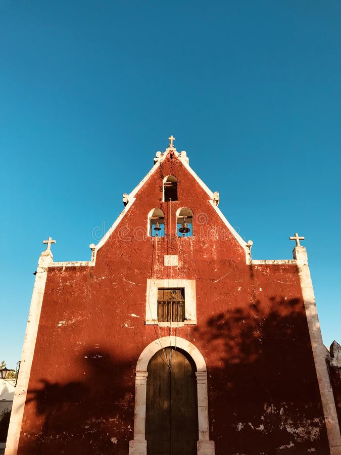 En gammal kyrka med burgundy väggar i hjärtan av Merida, Mexico - MERIDA - YUCATANEN royaltyfria bilder