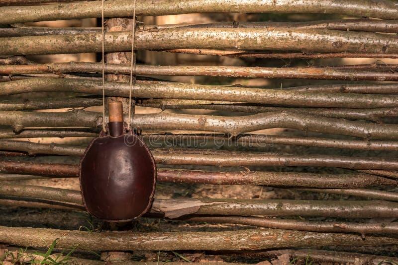en gammal lädervattenflaska hänger på ett staket som göras av filialer fotografering för bildbyråer