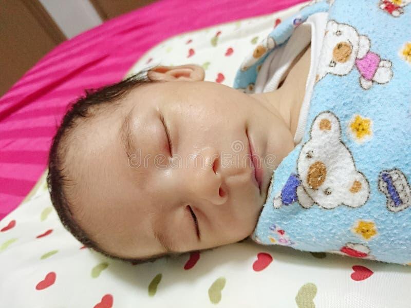 En gammal månad behandla som ett barn att sova royaltyfri foto