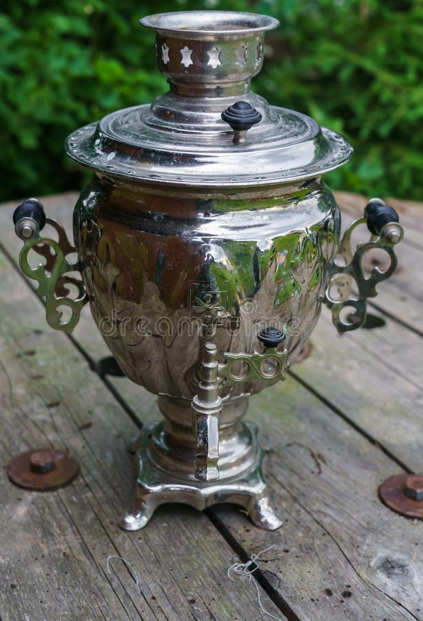 En gammal metallsamovar för framställning av te på en trätabell royaltyfria bilder