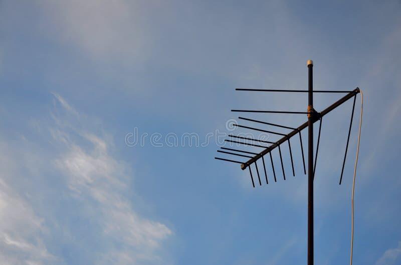 En gammal och rostig televisionantenn mot en molnig blå himmel arkivfoto