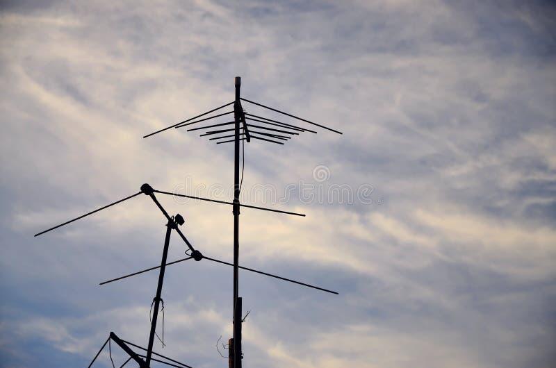 En gammal och rostig televisionantenn mot en molnig blå himmel royaltyfri fotografi