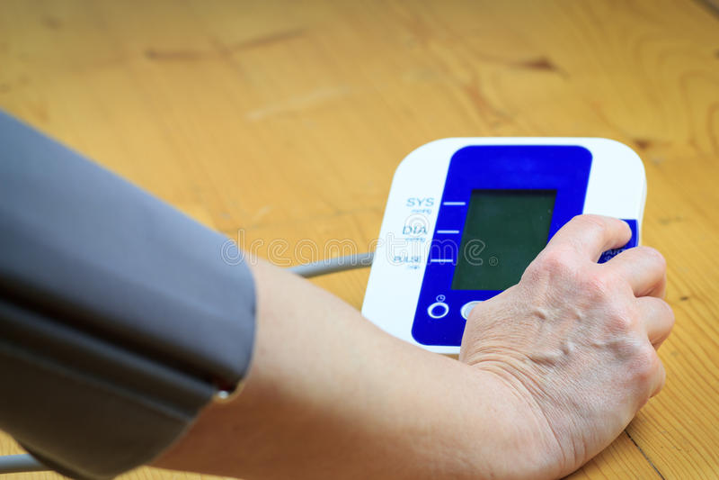 En gammal pensionär/kvinna förbereder att mäta blodtryck vid electr royaltyfri foto