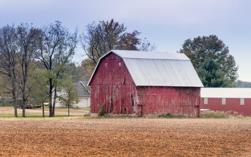 En gammal röd ladugård på familjlantgården royaltyfri foto