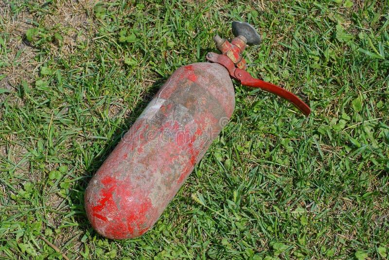 En gammal röd och smutsig brandsläckare ligger på det gröna gräset arkivbilder