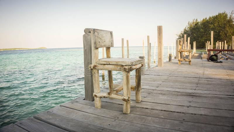 En gammal riden ut stol för trä på liten port med havsbakgrundslandskapet indonesia royaltyfri foto