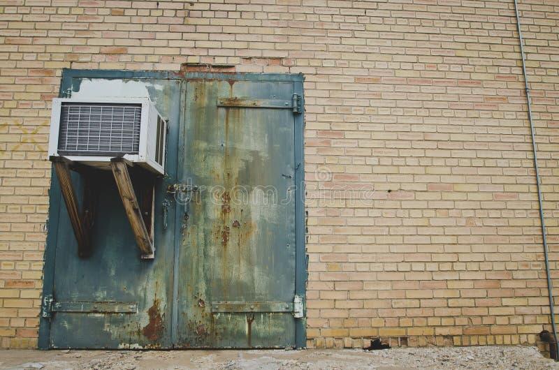 En gammal rostig grön dörr med en ac-enhet på den gamla fabriken royaltyfri fotografi