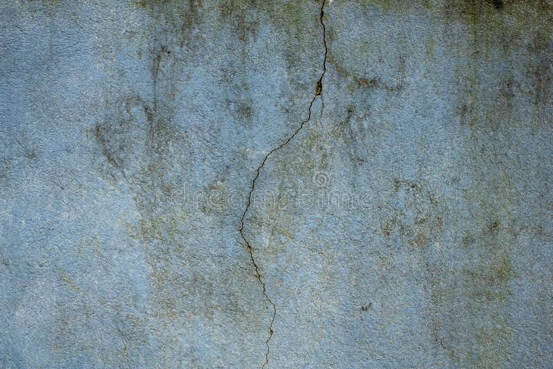En gammal smutsig blått-gräsplan vägg med en stor spricka och fläckar av smuts, formen och mossa ungefärlig textur konkret ungefä royaltyfria foton