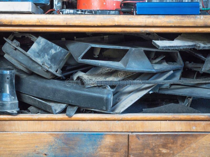 En gammal träask med olika apparater och motorfordondelar travde tillsammans på dess hyllor Övre sikt för slut på trä arkivfoto