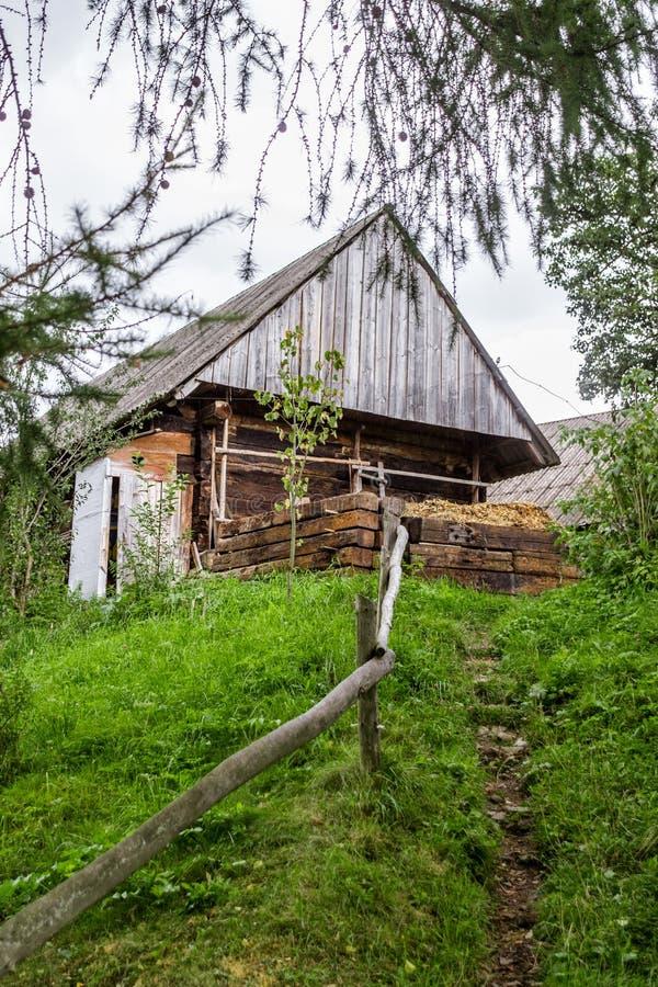 En gammal träladugård i europeisk by royaltyfri bild