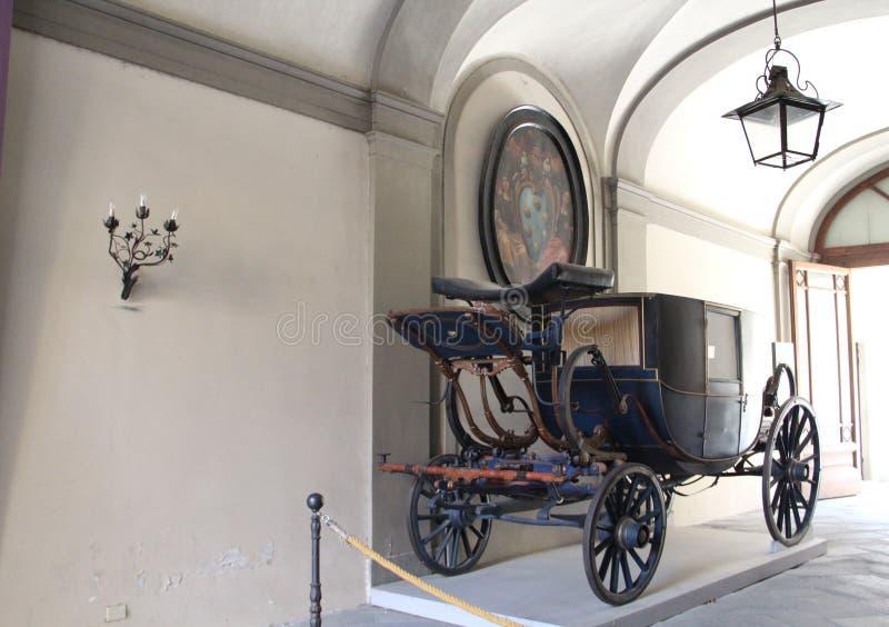 En gammal vagn, en lykta och en vägglampa mot en vit vägg och målningar i staden av Lucca, Italien royaltyfri foto